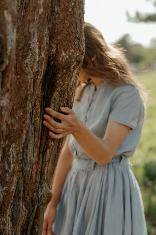 Woman in White Dress Leaning on Brown Tree