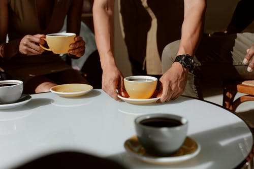 2 Person Holding Brown Ceramic Cups on White Table