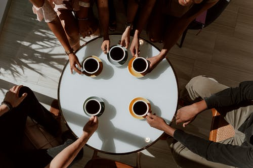 People Holding White Ceramic Mugs on Round Table