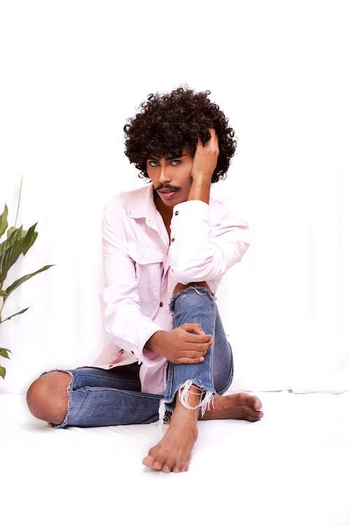 Woman in White Blazer and Blue Denim Jeans Sitting on White Floor