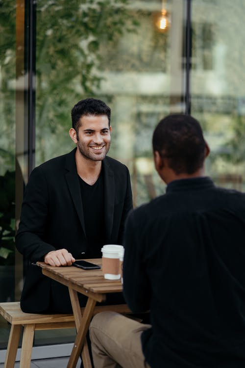 Cheerful diverse male friends having coffee break in outdoor cafe