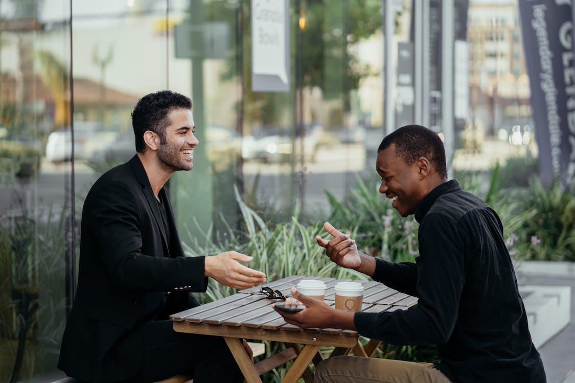 Man in Black Long Sleeve Shirt Sitting Beside Man in Black Long Sleeve Shirt