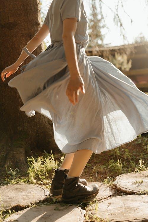 Woman in White Dress Walking on Green Grass