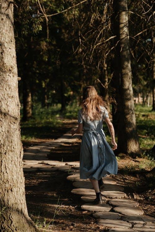 Girl in White Dress Standing Beside Tree