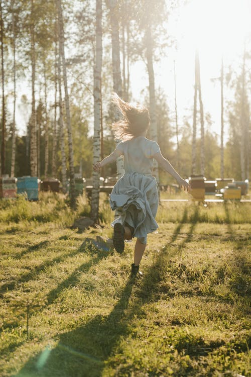 Girl in White Dress Running on Green Grass Field