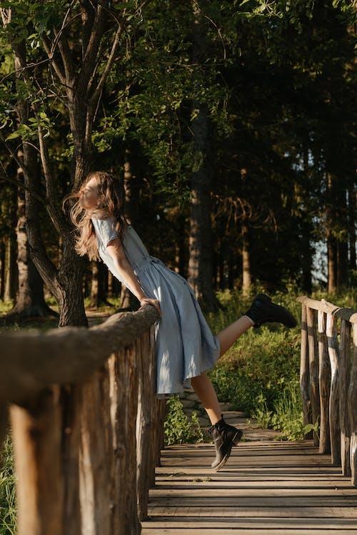 Woman in Blue Dress Standing on Brown Wooden Bridge