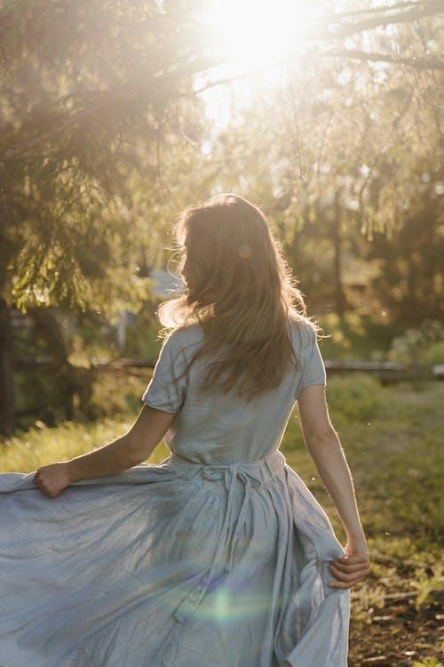 Girl in White Dress Sitting on Green Grass