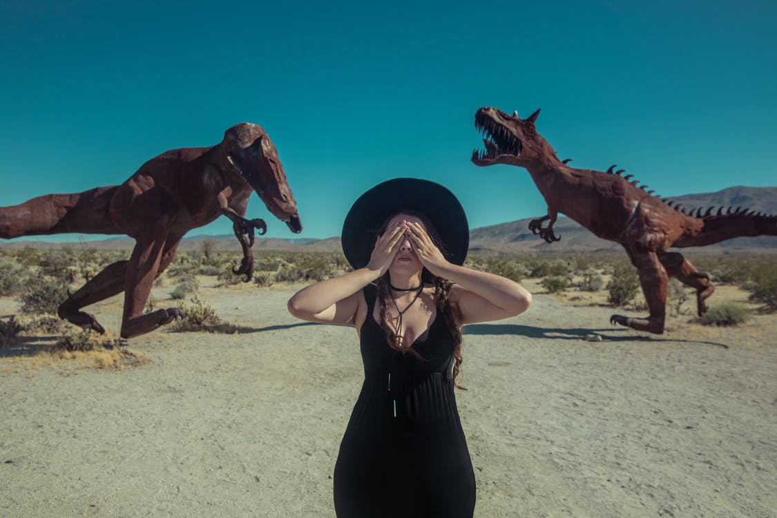 Woman in Black Tank Dress and Brown Cowboy Hat Standing on White Sand