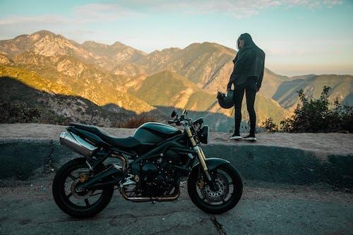 穿着黑色夹克和黑色裤子站在黑色摩托车旁边的人
