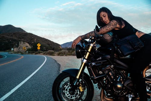 Woman in Black Shirt Riding Black Motorcycle on Road
