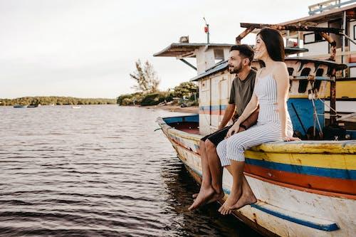 Joyful couple sitting on old boat and holding hands