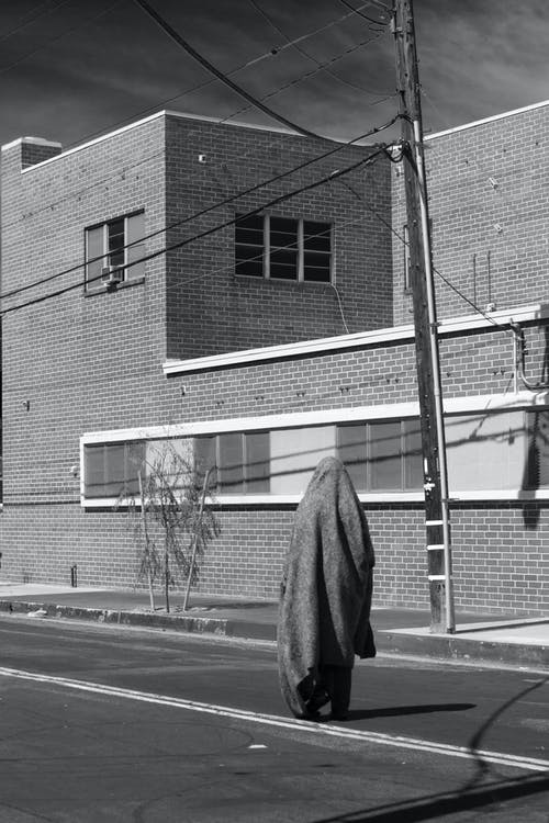Grayscale Photo of Person in Coat Standing Near Building