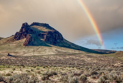 Scenery view of bright rainbow in cloudy sky over dry land with succulent plants and mountain
