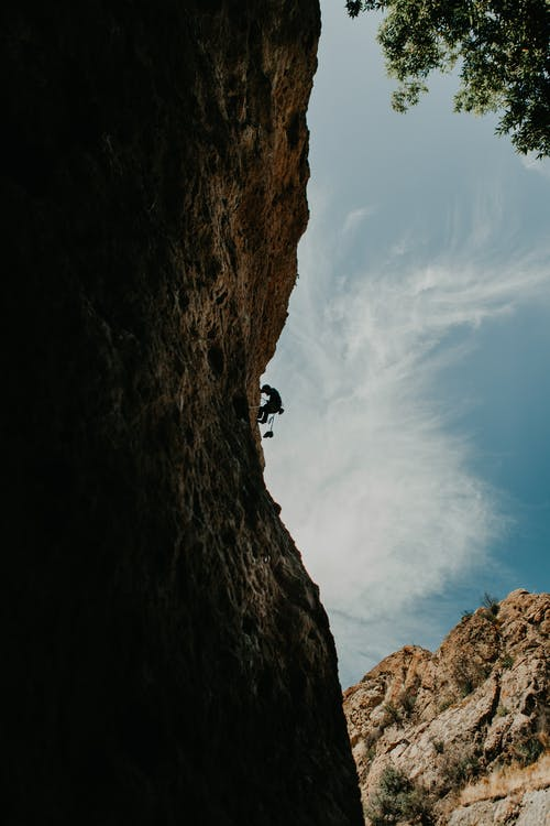 Person Climbing on Brown Rock Mountain