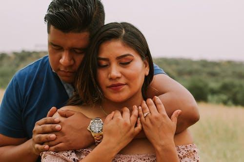 Loving Hispanic couple embracing in nature