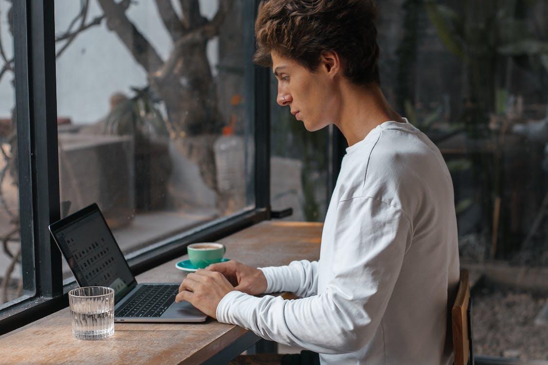Man in White Long Sleeve Shirt Using Laptop Computer
