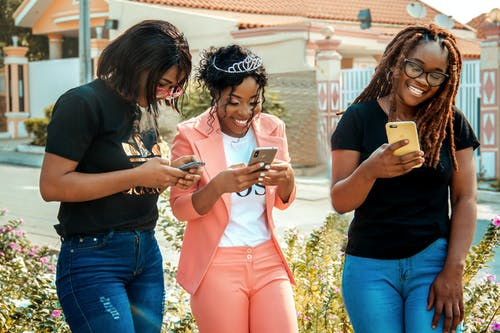 Happy ethnic women in trendy wear text messaging on cellphones on city street