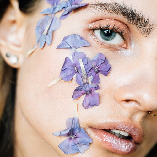 Woman With Purple Flower on Her Face
