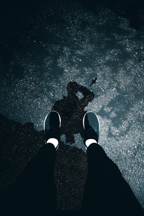 From above of legs and reflection of faceless person in black trousers and sneakers on wet pavement in daylight