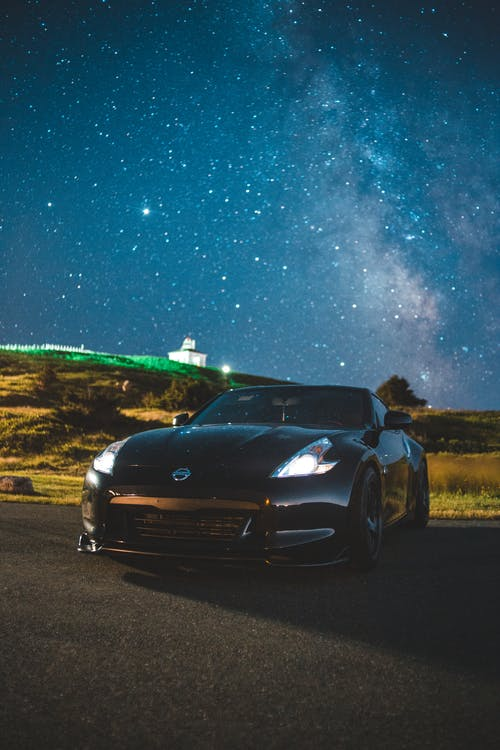 Modern coupe car with glowing headlights parked on asphalt road against bright night sky