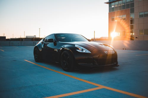 Stylish black car on parking area at sunset