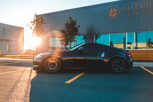 Contemporary new black auto on asphalt parking near house facade in town in shiny sunlight