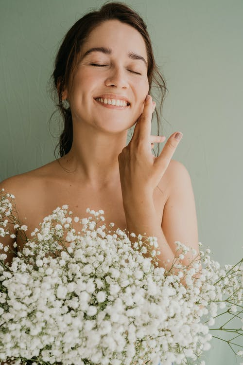 Smiling Woman Holding a Bouquet of White Flowers