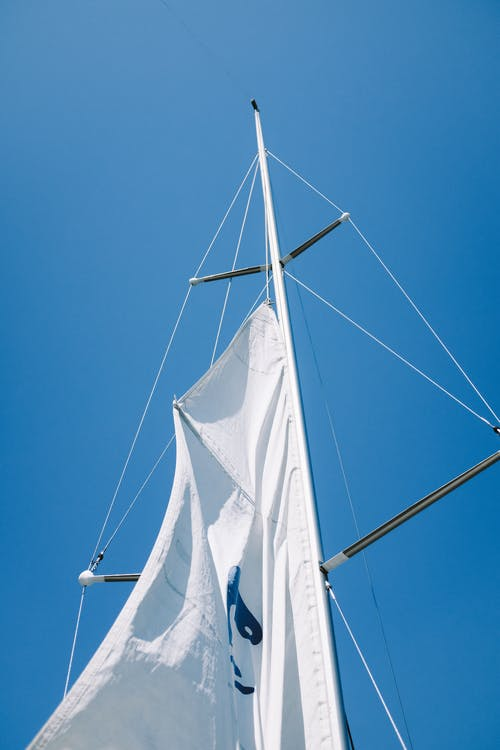 White Sail Boat on Blue Sky