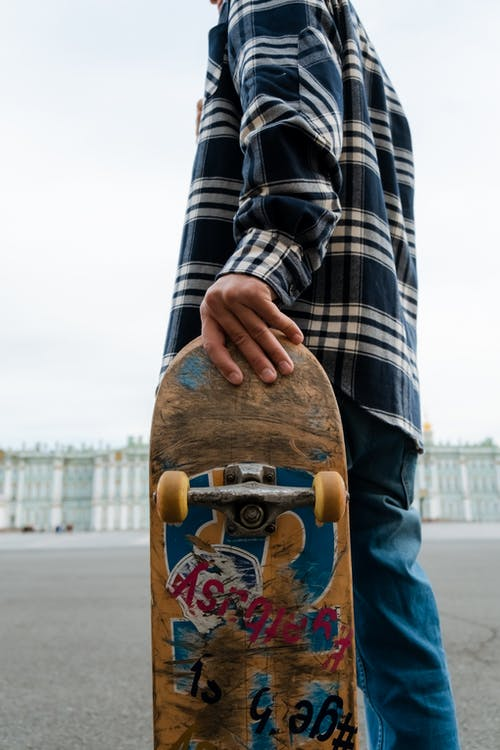 Person in Black and White Plaid Long Sleeve Shirt Holding Brown Wooden Skateboard