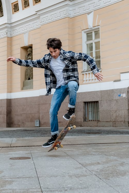 Man in Blue and White Plaid Dress Shirt Riding Skateboard