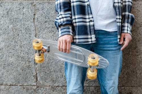 Person in Blue and White Plaid Long Sleeve Shirt and Blue Denim Jeans Holding Yellow Water