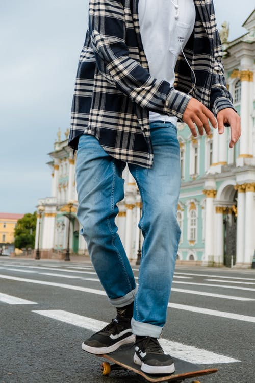 Person in Blue Denim Jeans and Plaid Shirt Standing on Road