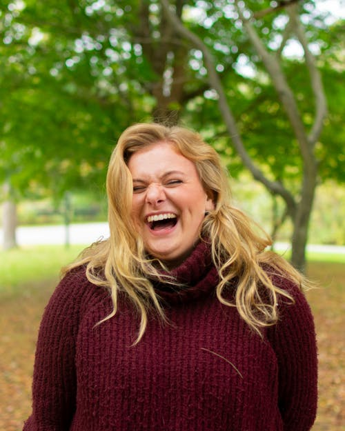 Woman Wearing a Sweater Laughing Out Loud