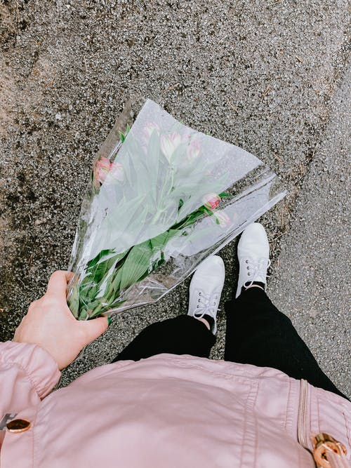 Anonymous person holding bouquet of flowers