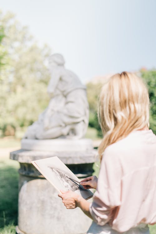 Woman in Long Sleeve Shirt Drawing a Statue