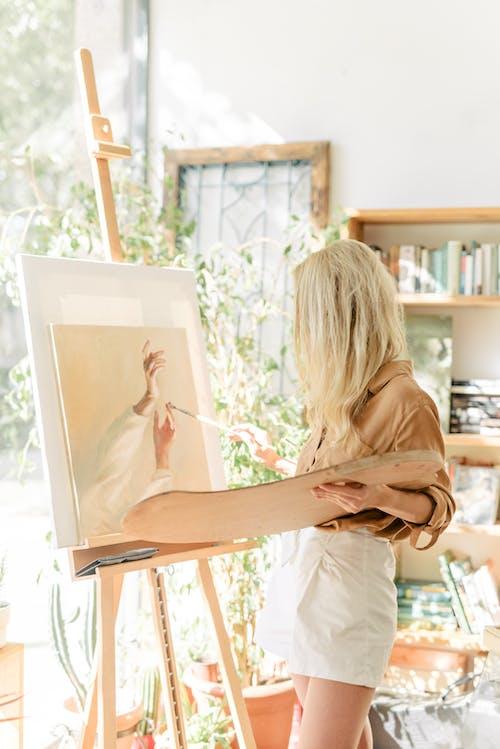 Женщина в белой рубашке с длинным рукавом сидит на коричневом деревянном стуле