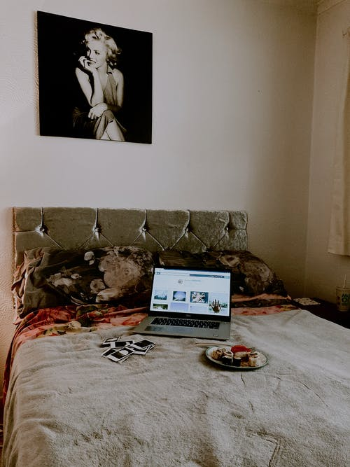 Laptop and plate on bed