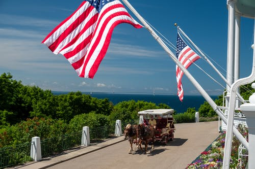 Free stock photo of american flags, blue water, carriage
