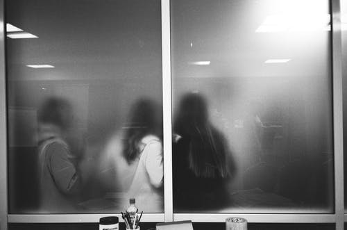 Stationery near window with unrecognizable girlfriends in building