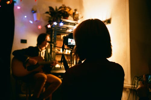 Unrecognizable female recording video of friend playing guitar on camera in flat with shiny garlands