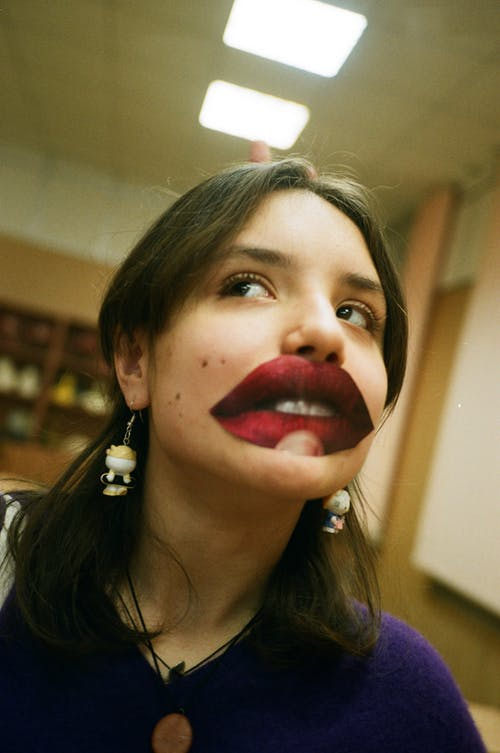 Funny adolescent in earrings with colorful decorative lips looking away under ceiling with glowing lamps
