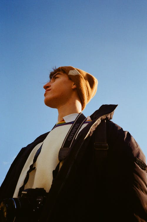 Dreamy photographer with photo camera under blue sky