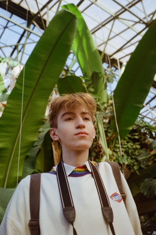 Serious male teenager relaxing in greenhouse