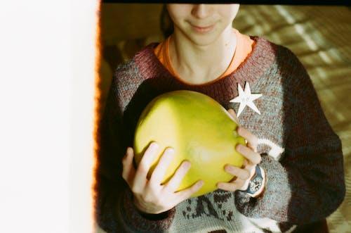 Unrecognizable person with ripe Citrus maxima fruit in hands
