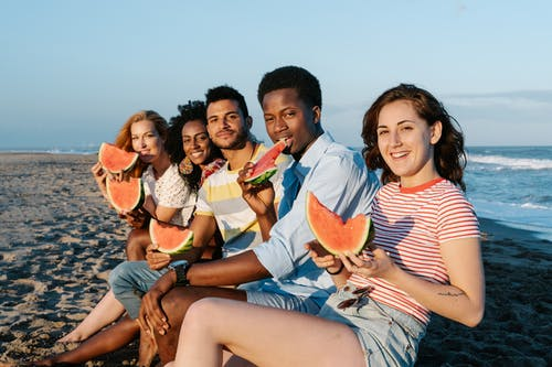 Glad diverse travelers eating watermelon on ocean beach
