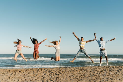 Excited multiethnic friends jumping above sandy sea beach in summer