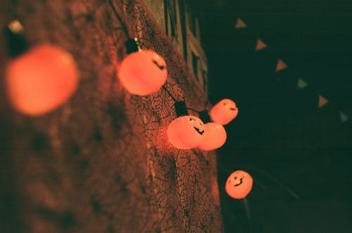 Glowing pumpkin lamps hanging on wall during Halloween celebration