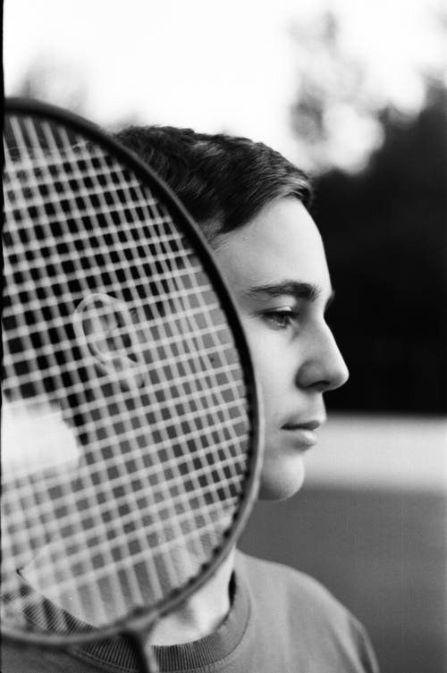 Pensive teen boy with badminton racket on court