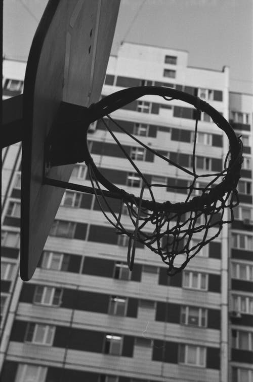 From below of black and white basketball hoop hanging on sports ground in city park near residential building