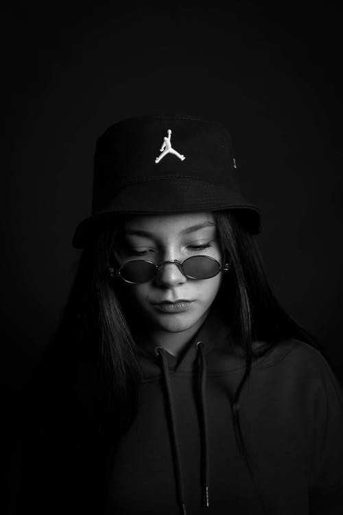 Wistful young woman in hat and sunglasses looking down